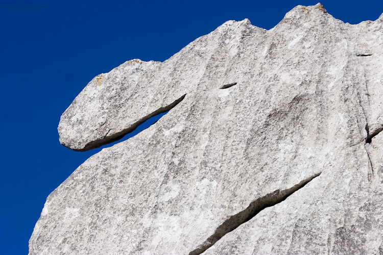 Low angle view of rock formation against clear blue sky in bijele stijene mountains in croatia