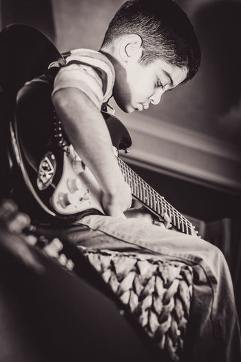 Close-up of boy playing guitar at home