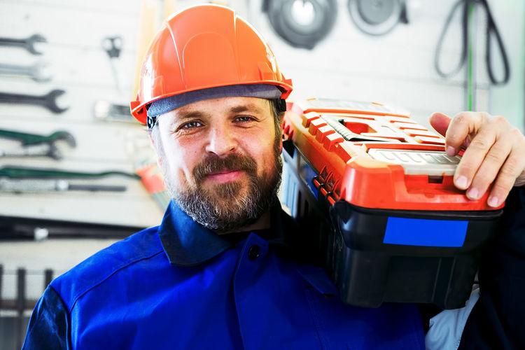 Portrait of smiling man wearing hardhat standing at workshop