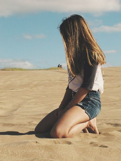 Side view of young woman kneeling on sand at beach against sky during sunny day