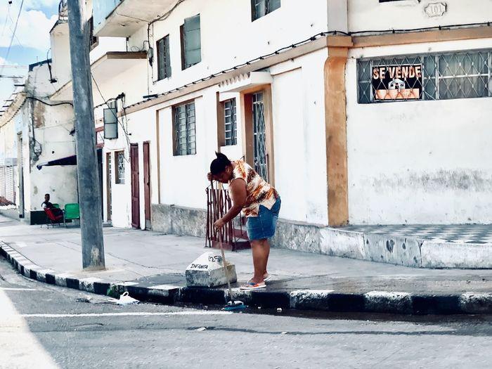 Full length of man holding umbrella on street against buildings in city