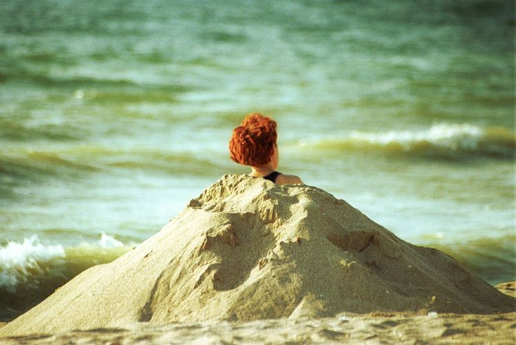 Optical Illusion Of Person Covered With Sand Against Sea