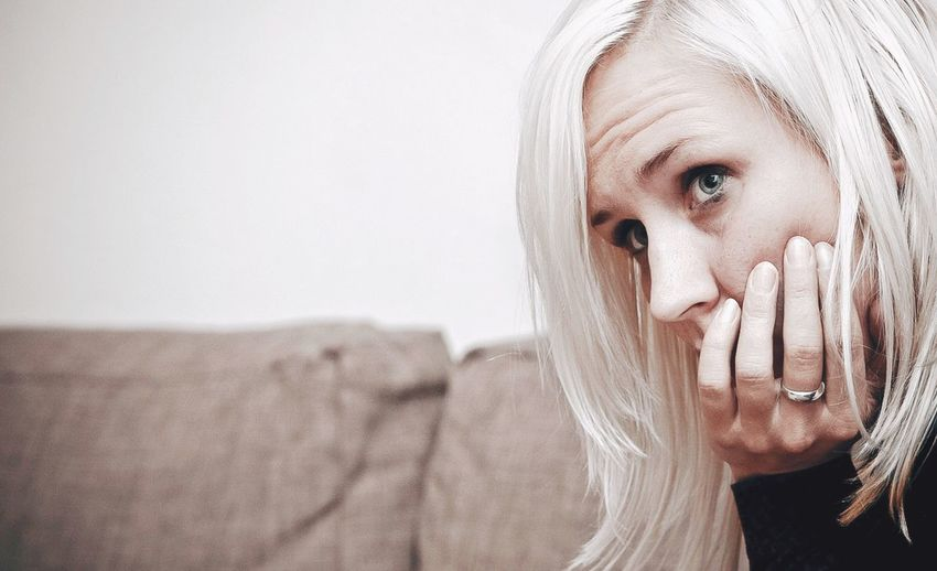 Close-up of thoughtful woman looking away at home