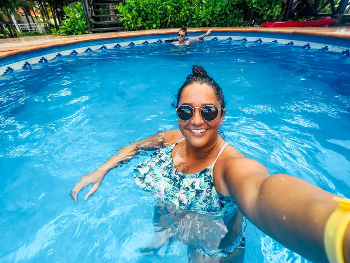 girl in the pool on vacation in Mexico Holiday Mexico Blue Day Fashion Front View Glasses Happiness Leisure Activity Lifestyles Looking At Camera Nature One Person Outdoors Pool Portrait Real People Smiling Sunglasses Swimming Pool Tropical Vacation Water Young Adult Young Women