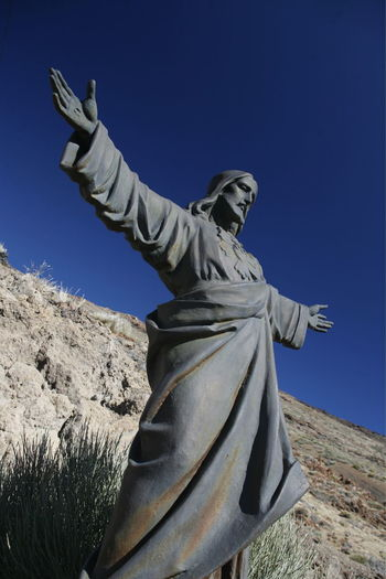 Low angle view of jesus christ statue against mountain