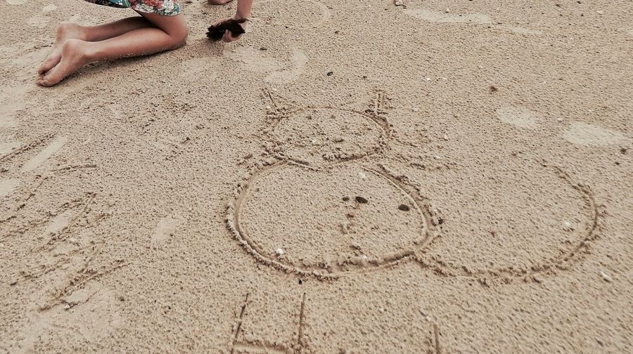 Low Section Of Girl Kneeling Beside Drawing In Sand