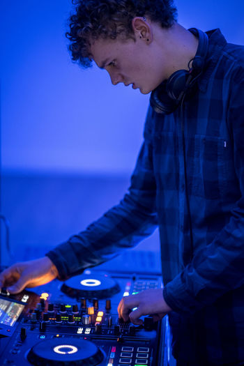 Young dj mixing music at nightclub