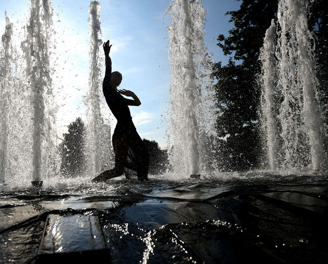 Silhouette man splashing water in fountain