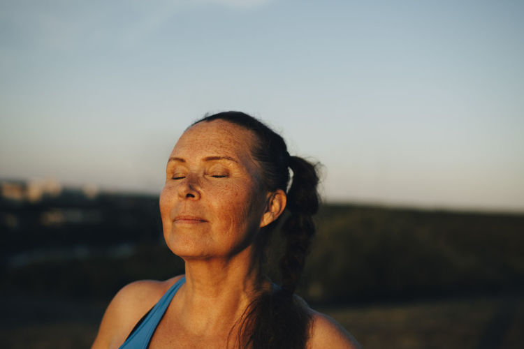 Portrait of woman looking at camera against sky during sunset