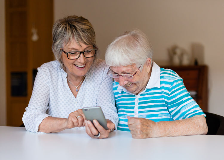 Senior Women Using Mobile Phone At Table In Home