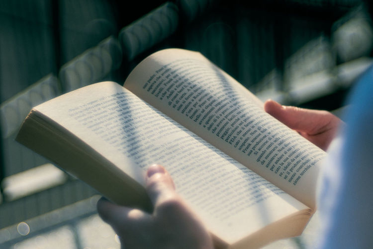 Cropped image of person holding book
