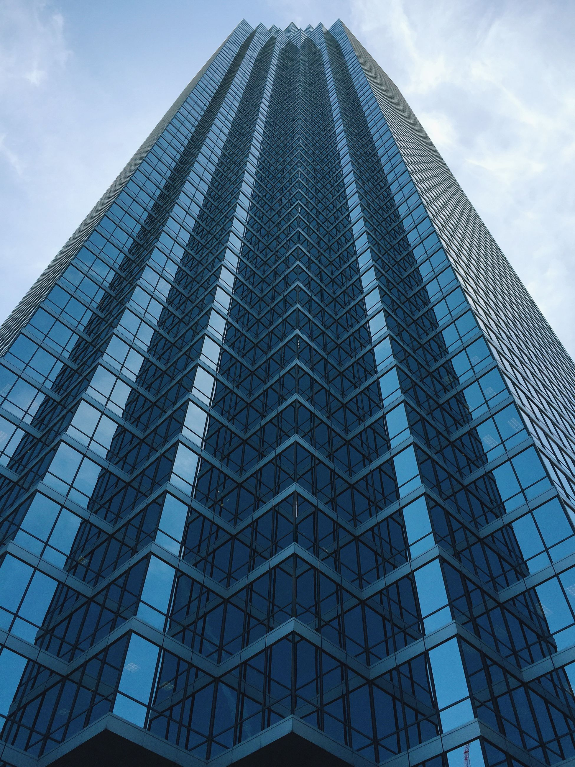 architecture, low angle view, building exterior, built structure, modern, office building, glass - material, city, tall - high, skyscraper, sky, reflection, tower, building, pattern, architectural feature, day, window, no people, outdoors