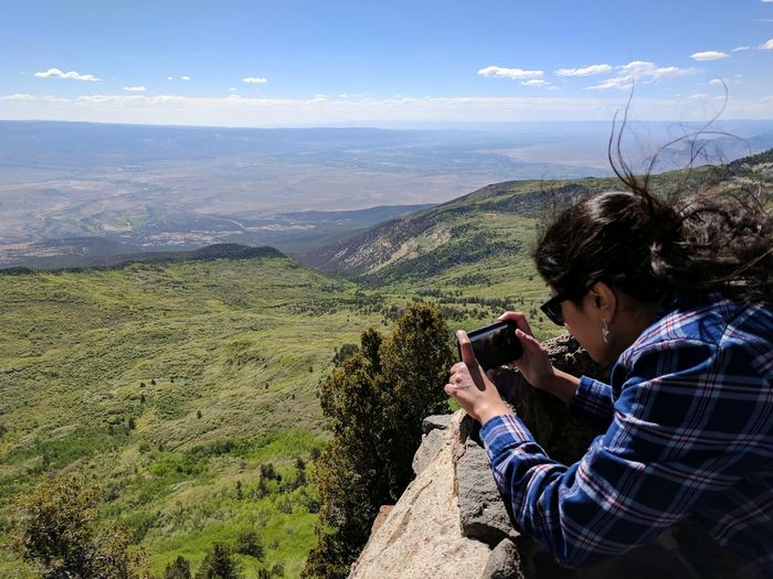 Woman Photographing Landscape With Mobile Phone Against Sky