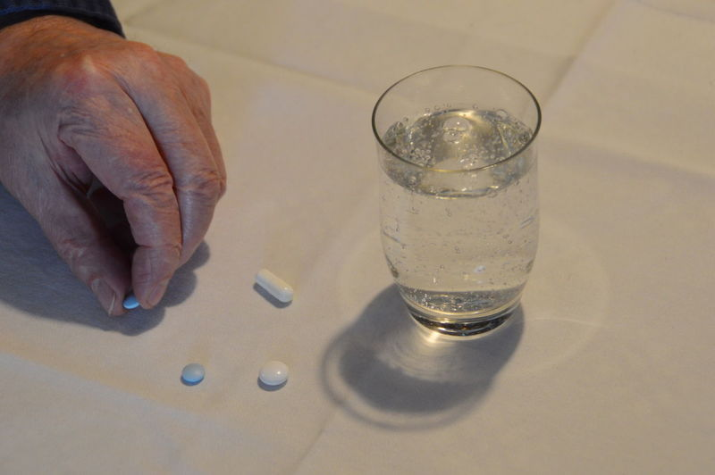 Cropped image of man hand holding pill by drinking glass on table