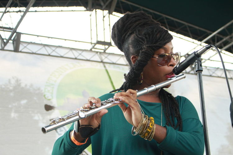 Young Woman Playing Flute In Front Of Microphone