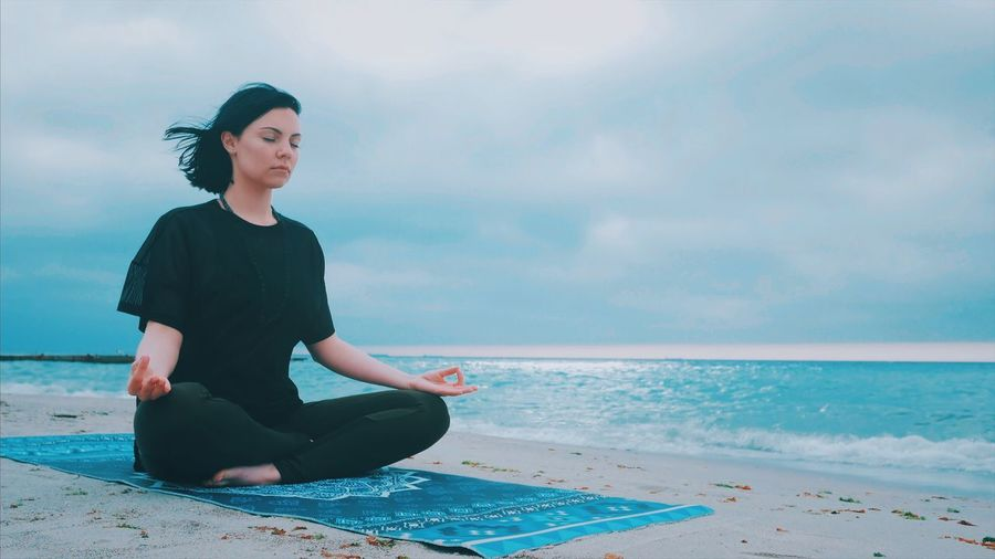 Woman Meditating While Sitting On Shore At Beach Against Sky