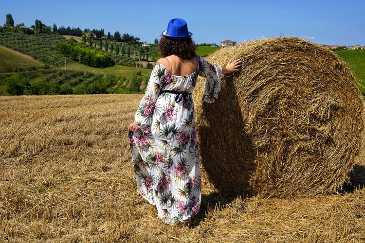 beautiful woman between round bales From Behind Hat Woman Adult Agriculture Bale  Clothing Day Farm Field Grass Hairstyle Hay Land Landscape Nature One Person Outdoors Plant Real People Rear View Rural Scene Sky Women