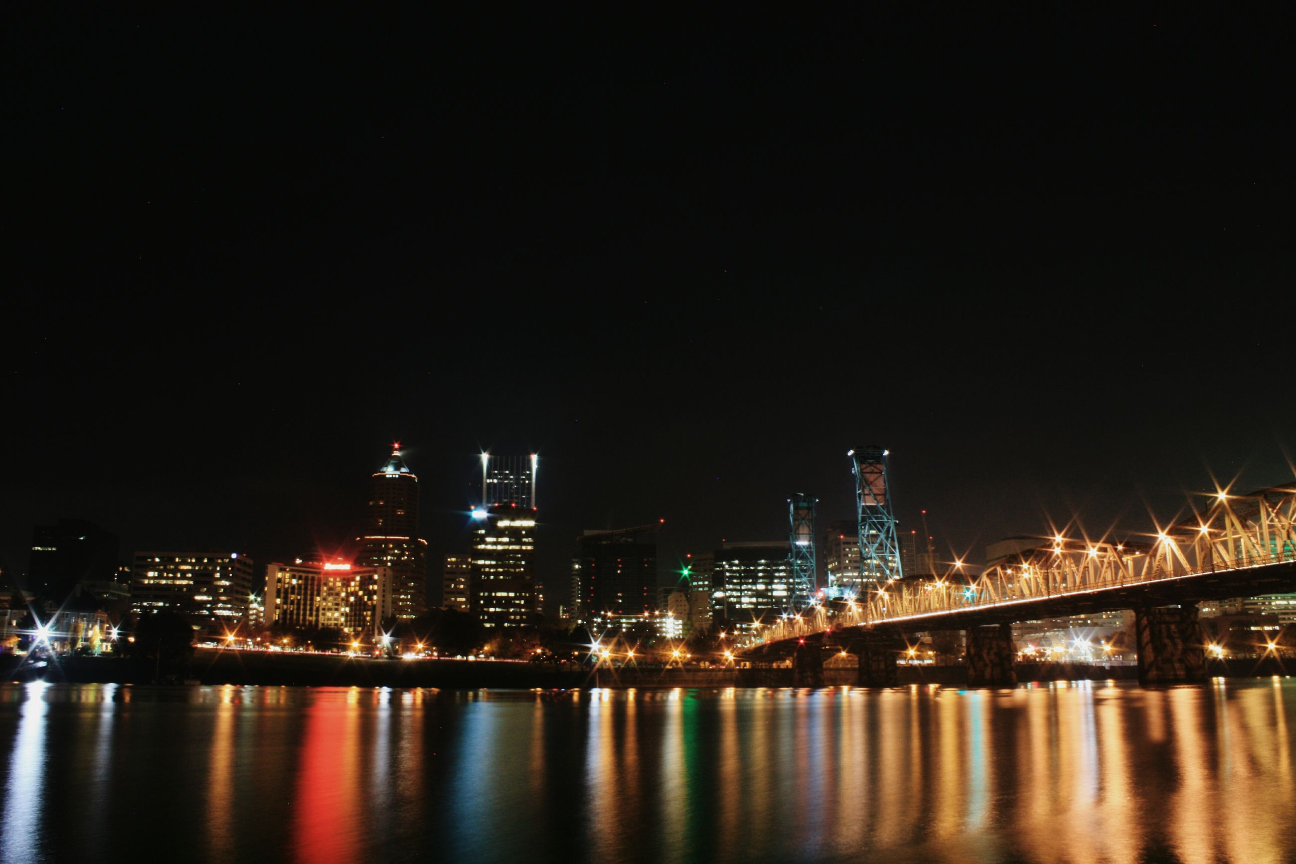 illuminated, night, city, building exterior, architecture, water, waterfront, built structure, cityscape, skyscraper, river, reflection, urban skyline, modern, office building, clear sky, tall - high, copy space, sea, tower