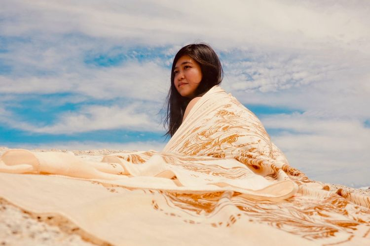 Young woman wrapped in blanket on sand at beach against sky