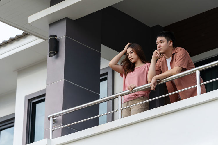 Low angle view of couple standing on staircase