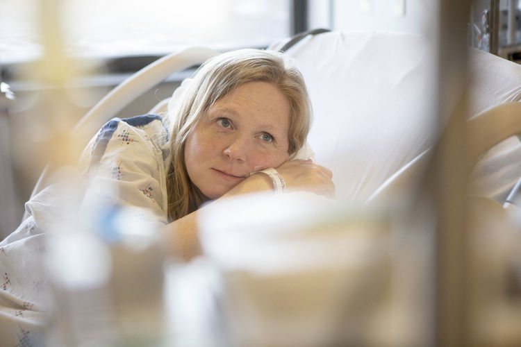 A pregnant woman rests in a hospital bed between contractions before giving birth. Women Portrait Relaxation Happiness Smiling Beautiful Woman Headshot Indoors  Hairstyle Birth Blond Hair Pregnancy Medical Females Adult Patient Labor Lying Down Front View Lifestyles Looking At Camera Selective Focus One Person Casual Clothing Healthcare And Medicine Beautiful