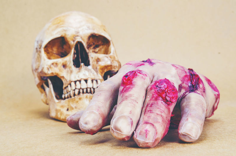 Close-up of hand and skull against beige background