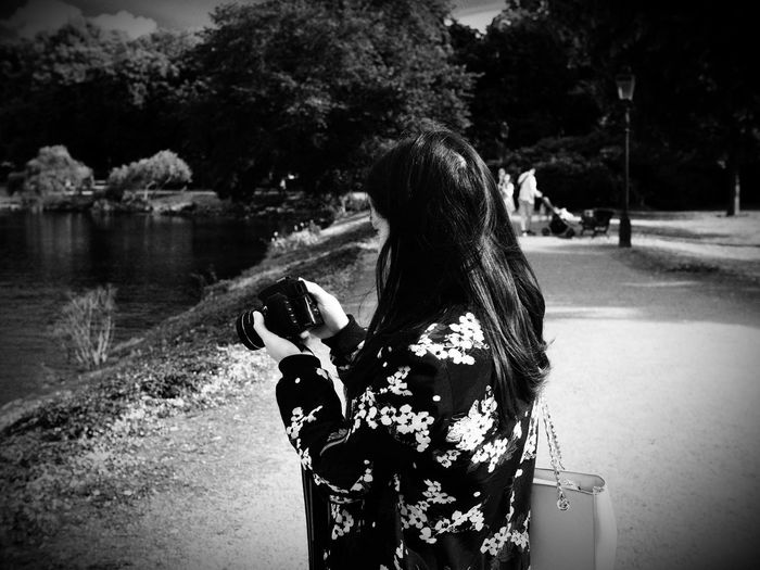 Side View Of Woman Holding Camera On Street By Lake During Sunny Day