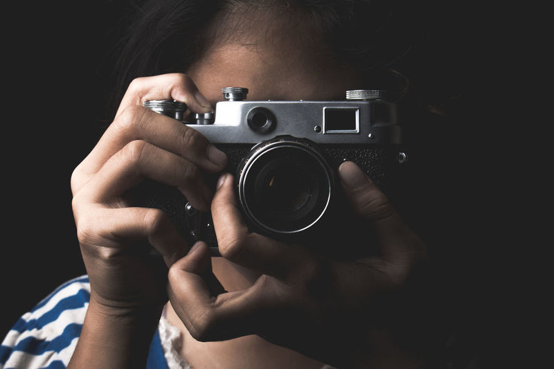 Close-up of girl photographing with camera against black background