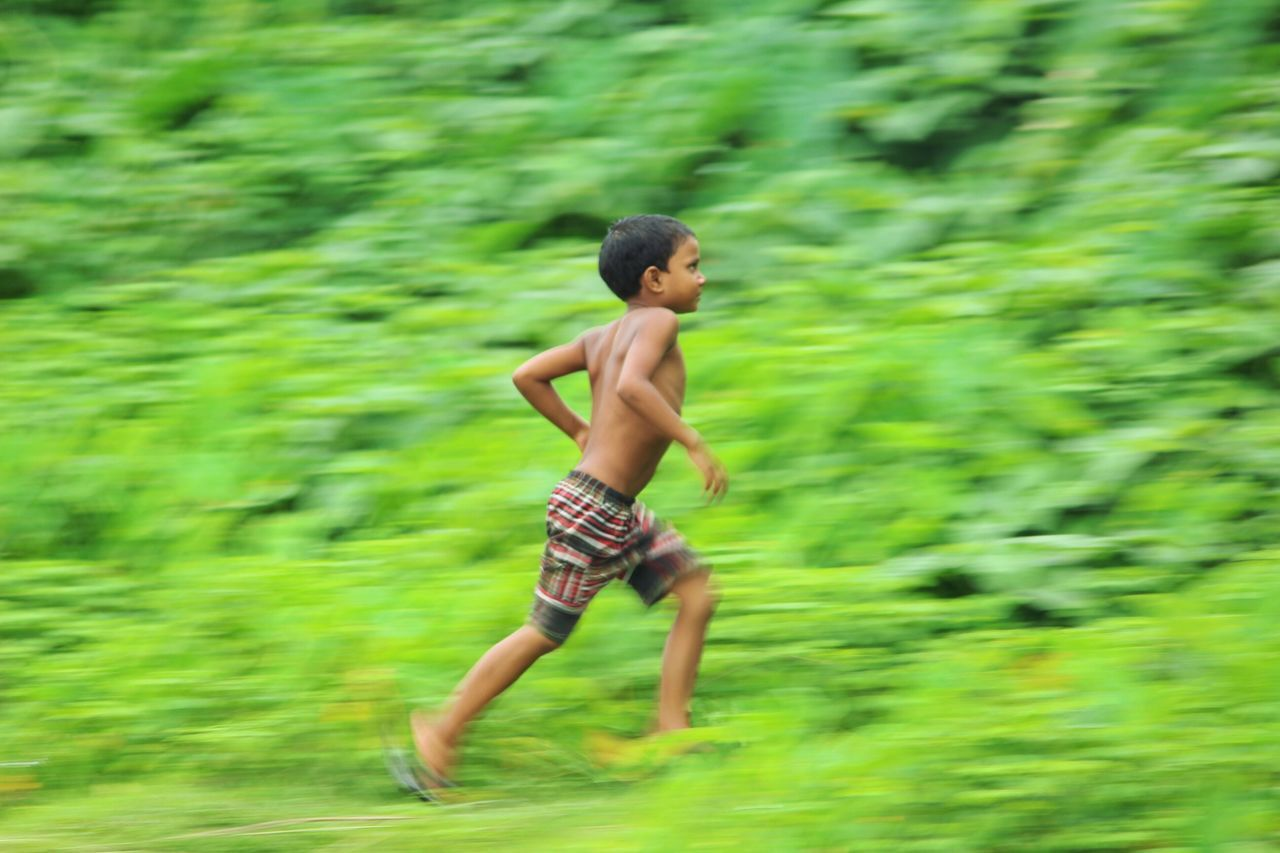 Blurred motion of shirtless boy running on field
