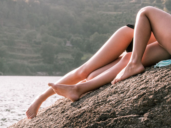 Low section of woman relaxing on rock