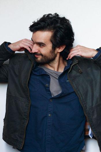 Smiling young man holding jacket against white wall