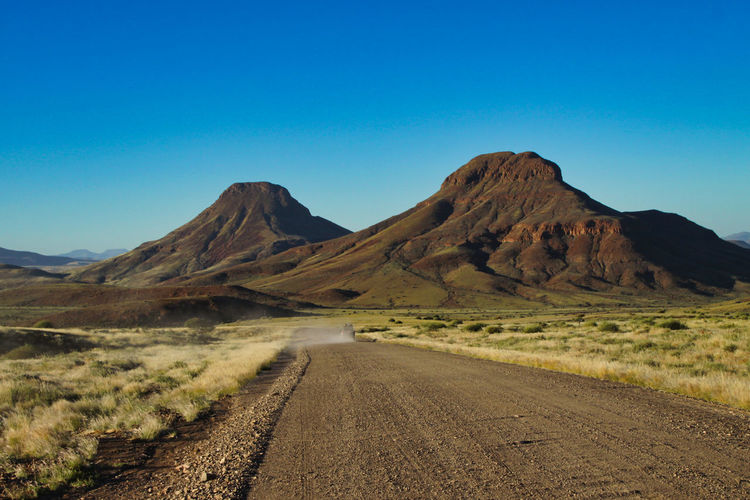 Dirt road amidst mountains against clear sky