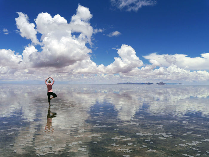 Rear View Of Woman Practicing Yoga In Sea Against Cloudy Sky