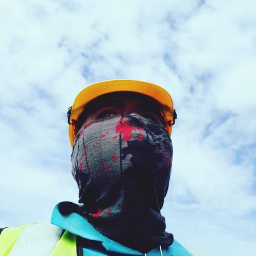 Low angle view of man wearing mask and hardhat against cloudy sky
