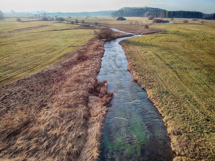 High angle view of river flowing amidst field