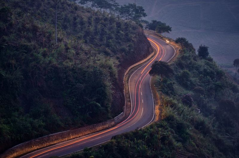 High Angle View Of Light Trails On Mountain Road During Sunset