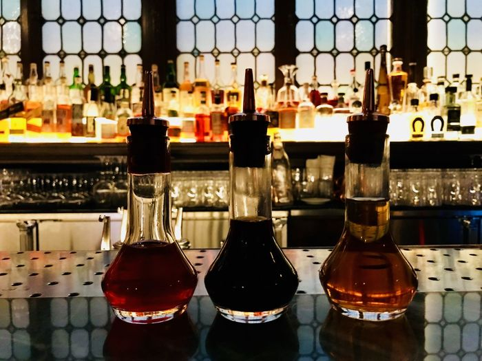 Bitters at the Bar, New York. Bar Counter Bar Countertop Choices Colored Glass Bitters Refreshment Drink Food And Drink Container Alcohol Bottle Indoors  Glass - Material No People Table Close-up Bar - Drink Establishment Still Life Glass Focus On Foreground Transparent Side By Side Household Equipment Window