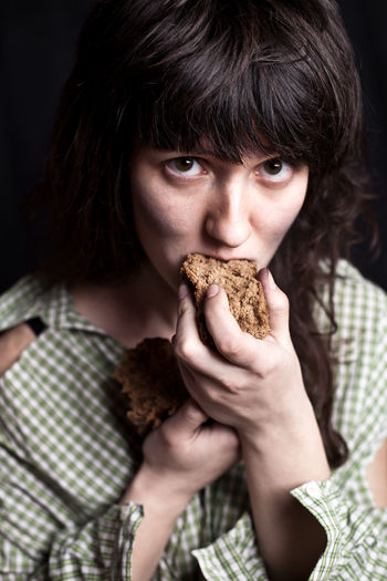 Portrait of poor woman eating bread