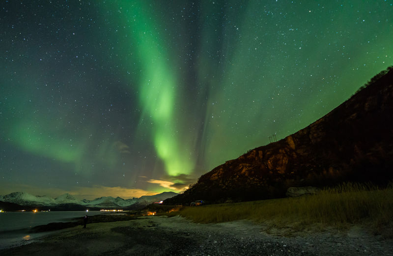 Scenic View Of Aurora Polaris Above Lake And Mountains At Night