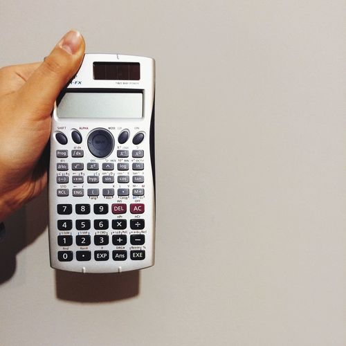Cropped image of woman holding retro calculator