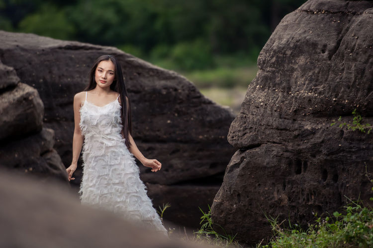 Portrait of young woman standing by rocks