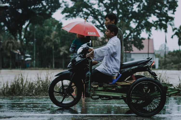 Side view of man riding motorcycle by people walking on wet road during rainy season