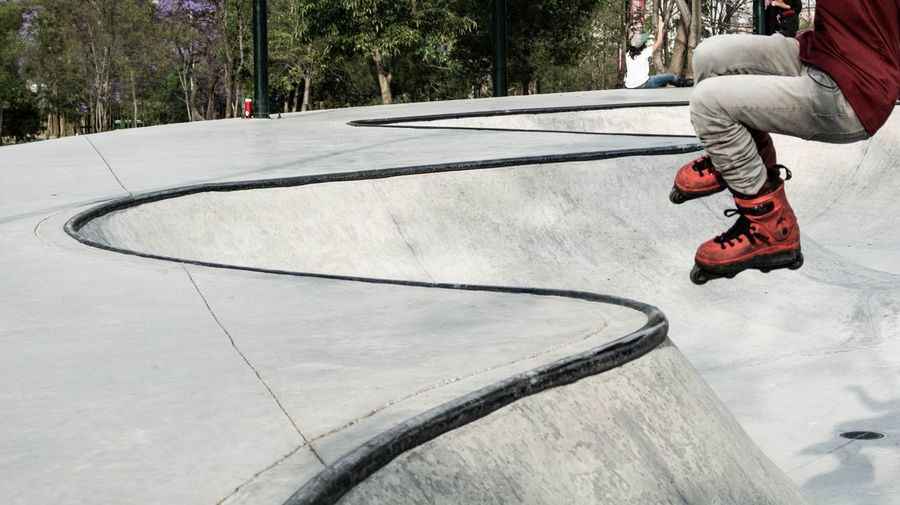Low section of man roller skating at park