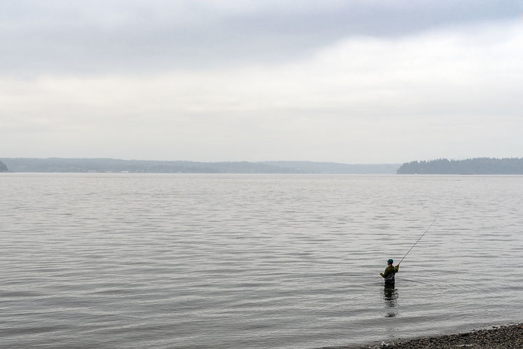 Fly fishing in Puget sound near Seattle under overcast sky. Fly Fishing Puget Sound Seattle, Washington Beauty In Nature Cloud - Sky Day Leisure Activity Lifestyles Men Nature Nature Conservancy Non-urban Scene One Person Outdoors Real People Scenics - Nature Sea Sky Tranquil Scene Tranquility Travel Destinations Vacation Water Waterfront