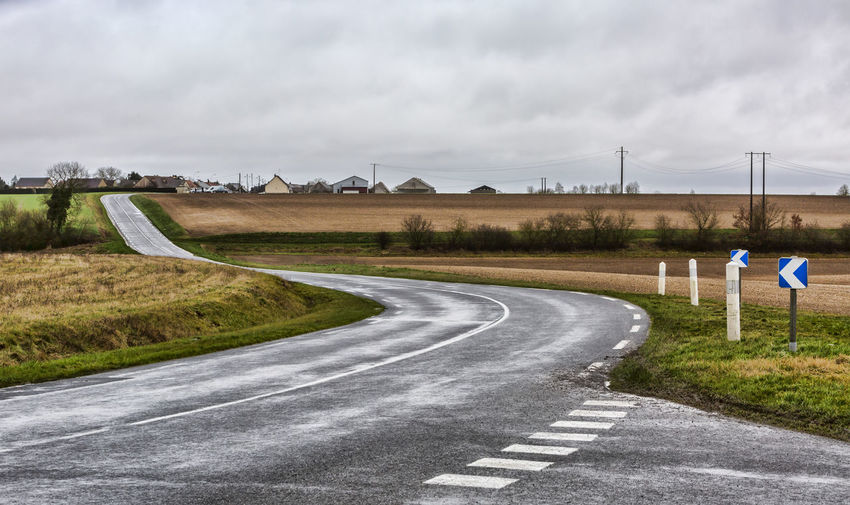 Image of an empty winding road in a countryside region of France in a bad weather day. Road Sign Transportation Direction Environment Sky Cloud - Sky The Way Forward Nature Road Sign Road Marking Country Road Curve Outdoors Wind Country Chateau-Renard Countryside Landscape Countryside Landscape Asphalt Asphalt Road