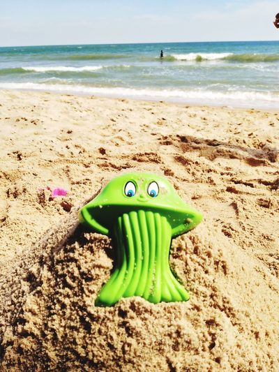Green toy on sand at beach against sky