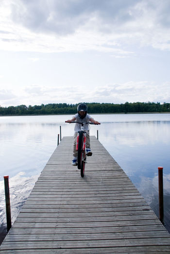 Activity Beauty In Nature Bicycle Bridge Cloud - Sky Day Full Length Lake Leisure Activity Lifestyles Nature One Person Outdoors Pier Real People Reflection Sky The Way Forward Transportation Water Wood - Material