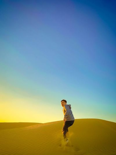 Man standing in desert against clear sky