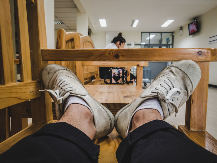 Low section of man sitting on wooden floor
