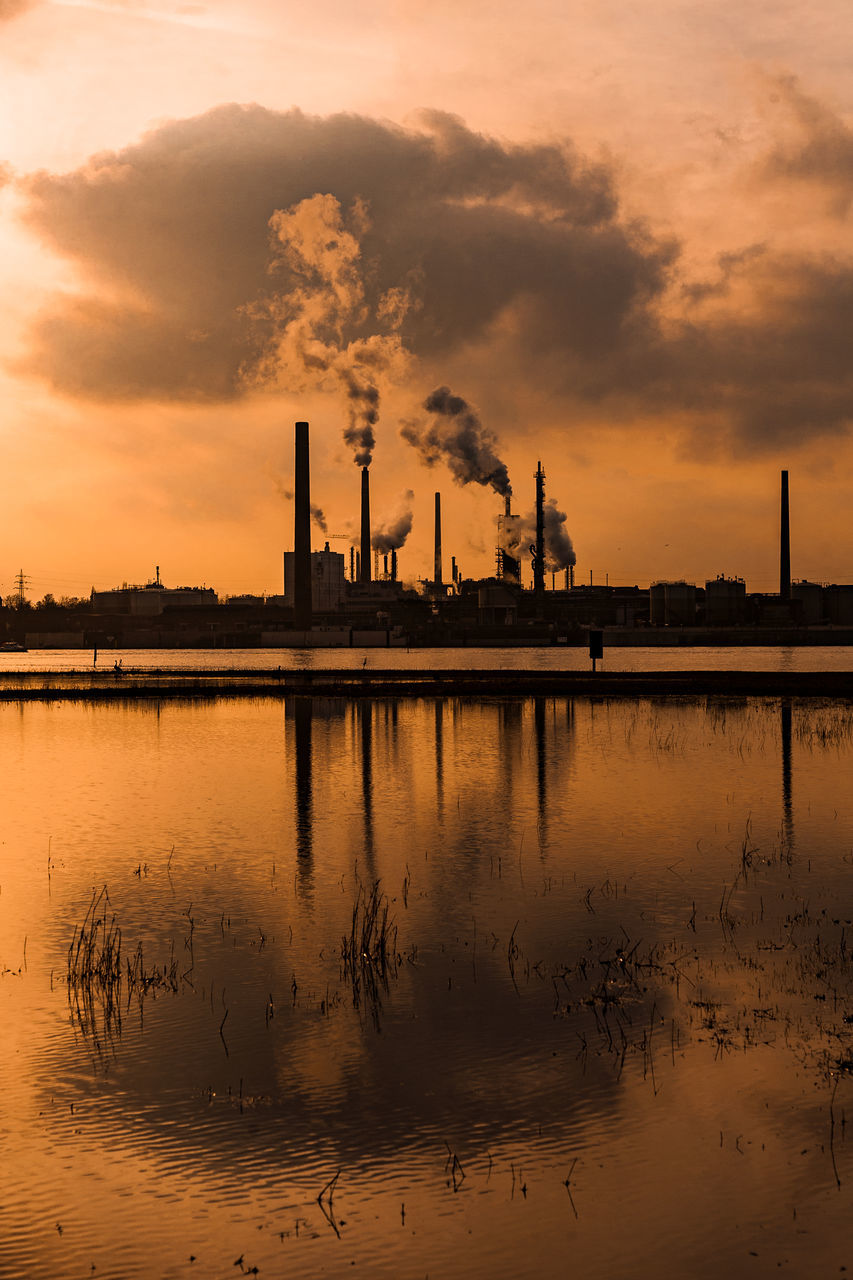 factory, smoke stack, industry, sky, reflection, sunset, building exterior, environmental issues, water, smoke - physical structure, pollution, built structure, cloud - sky, architecture, nature, environment, emitting, chimney, waterfront, no people, air pollution, outdoors, fumes, ecosystem, atmospheric